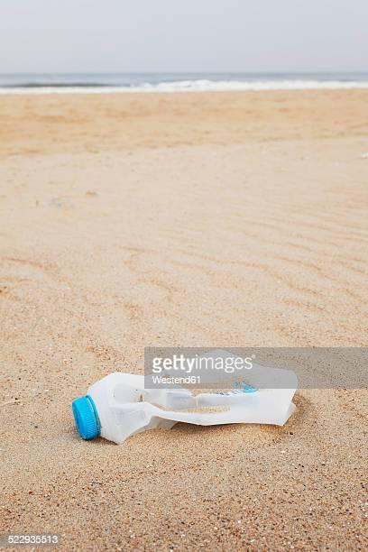 Belgium, empty plastic bottle lying on sandy beach at North Sea coast