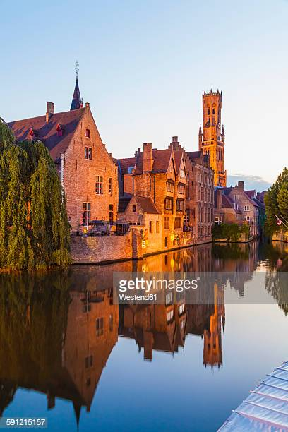 belgium, flanders, bruges, old town, rozenhoedkaai, canal and belfry tower in the evening - bruges stock pictures, royalty-free photos & images
