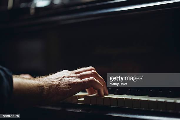 Belgium, Flanders, West Flanders, Brugge, Close-up of pianist's hand on piano keyboard