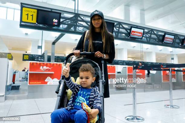 Belgium football team Thomas Meunier's girlfriend Deborah Panzokou and their son Landrys pose for a photograph before the departure of a fan flight...