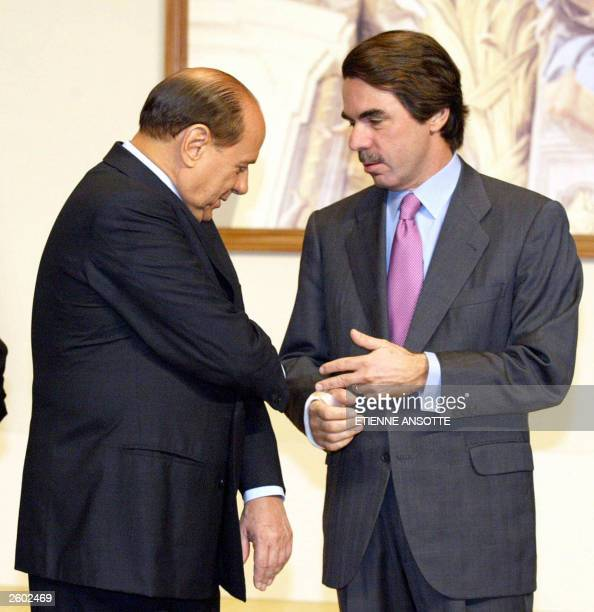 Italian Prime Minister and President of the European Council Silvio Berlusconi shows his arm he hurt after falling the day before to Spanish Prime...