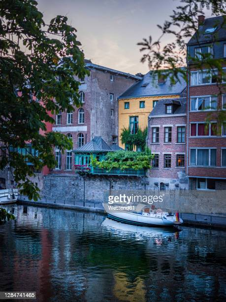 belgium, namur province, namur, motorboat moored along city canal stretching in front of row of townhouses - ナミュール州 ストックフォトと画像