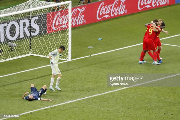 Belgium players celebrate their team's third goal while Japan goalkeeper Eiji Kawashima looks dejected before the end of a World Cup roundof16 match...