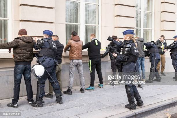 Belgium police officers arrest protestors during a demonstration of the yellow vests against the rising of the fuel and living costs in Brussels on...