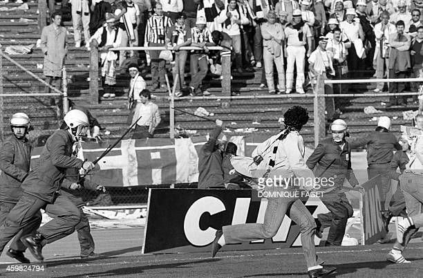 Belgium policemen run after Italian fans on May 29 1985 in Heysel stadium in Brussels as violence has broken out one hour before the European...