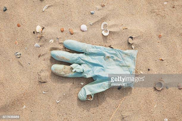 belgium, rubber glove lying on sandy beach at north sea coast - washing up glove stock pictures, royalty-free photos & images
