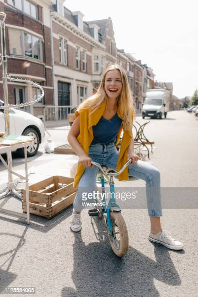 belgium, tongeren, happy young woman on a children's bicycle on an antique flea market - flea market stock pictures, royalty-free photos & images