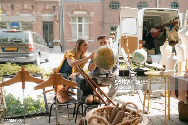 belgium, tongeren, young couple examining globe on an antique flea market - flea market stock pictures, royalty-free photos & images