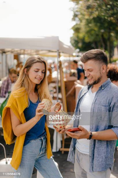 belgium, tongeren, young couple with tin cans on an antique flea market - flea market stock pictures, royalty-free photos & images
