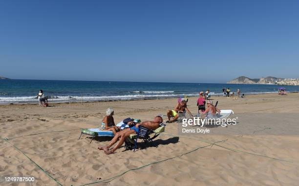 Belgium tourists take the sun in their roped off areas at Levante beach after the town's beaches were reopened after three months of closure due to...