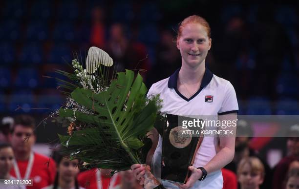 Belgium's Alison Van Uytvanck celebrates with her trophy after she won her final match of the WTA Hungarian Open Ladies' tennis tournament against...