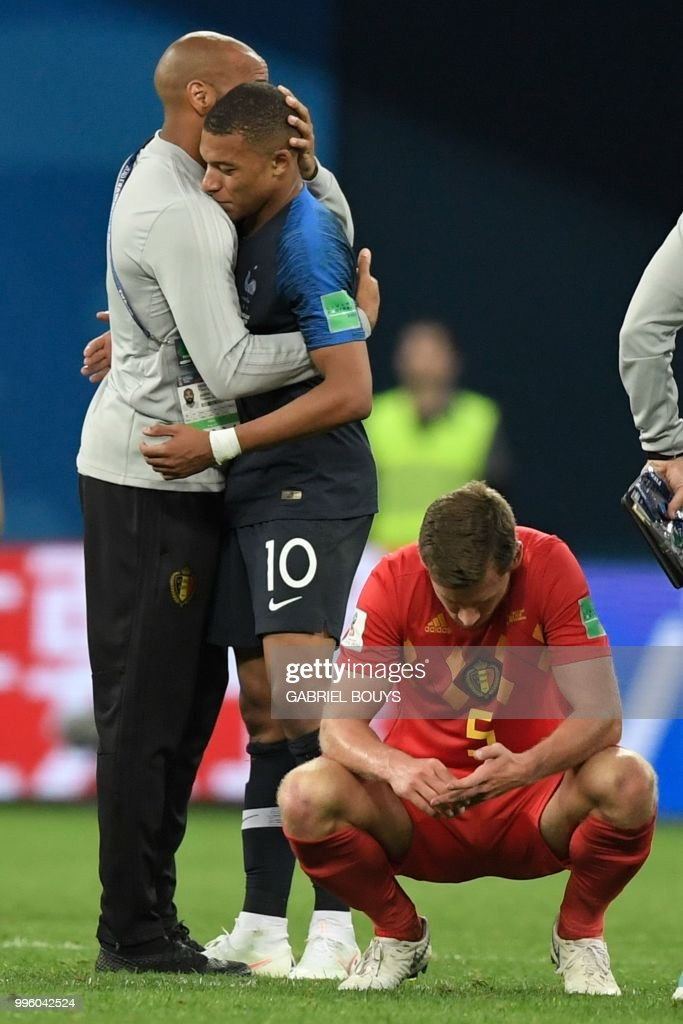 TOPSHOT - Belgium's assistant coach Thierry Henry (L) congratulates France's forward Kylian Mbappe as Belgium's defender Jan Vertonghen reatcs after the Russia 2018 World Cup semi-final football match between France and Belgium at the Saint Petersburg Stadium in Saint Petersburg on July 10, 2018. - France reached the World Cup final on Tuesday after a second-half header from Samuel Umtiti gave them a 1-0 win against Belgium. (Photo by GABRIEL BOUYS / AFP) / RESTRICTED