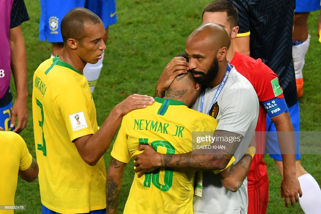 Belgium's assistant coach Thierry Henry (R) hugs Brazil's forward Neymar at the end of the Russia 2018 World Cup quarter-final football match between Brazil and Belgium at the Kazan Arena in Kazan on July 6, 2018. (Photo by SAEED KHAN / AFP) / RESTRICTED