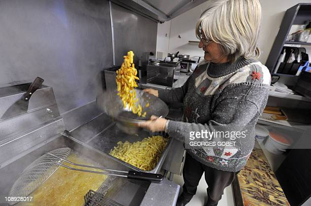 """""""Belgium's beloved chip stall fights to survive"""" by Laurent ThometJosiane Devlaeminck prepares Belgian fries at the Atomium """"fritkot"""", the Flemish..."""