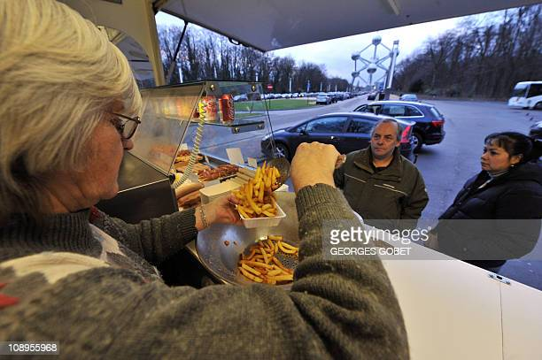 'Belgium's beloved chip stall fights to survive' by Laurent ThometJosiane Devlaeminck serves Belgian fries into a tray at the Atomium 'fritkot' the...
