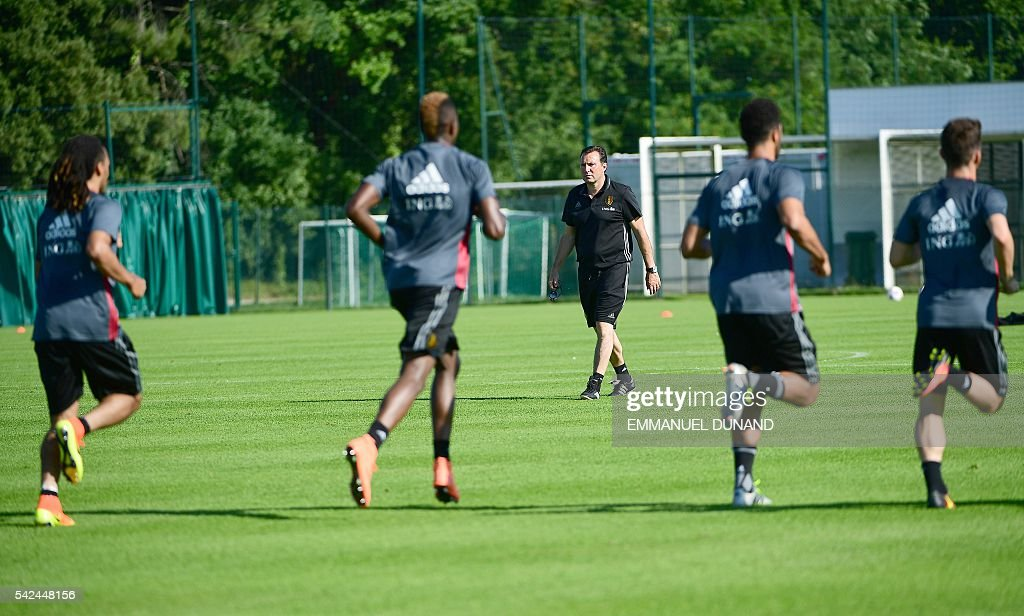 Belgium's coach Marc Wilmots (C) looks at players taking part in a training session for the altrenate players during the Euro 2016 football tournament at Le Haillan, western France, on June 23, 2016. / AFP / EMMANUEL