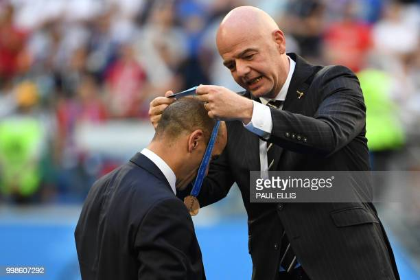 Belgium's coach Roberto Martinez receives his bronze medal from FIFA president Gianni Infantino after winning the Russia 2018 World Cup playoff for...
