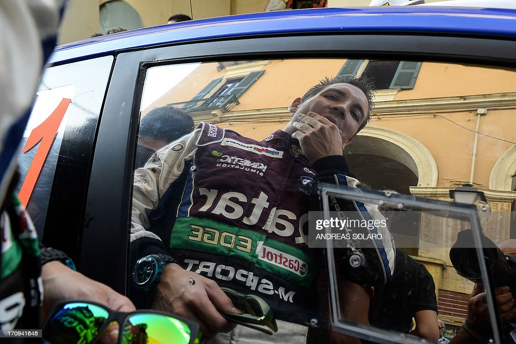 Belgium's co-driver Nicolas Gilsoul is reflected in the window of their Ford Fiesta RS WRC, during the opening ceremony of the FIA World Rally Championship of Italy in Sassari, on the Italian island of Sardinia on June 20, 2013.