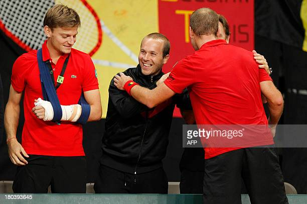 Belgium's David Goffin, Olivier Rochus and Steve Darcis celebrate after Darcis won his tennis match against and Israel's Dudi Sela, in the World...