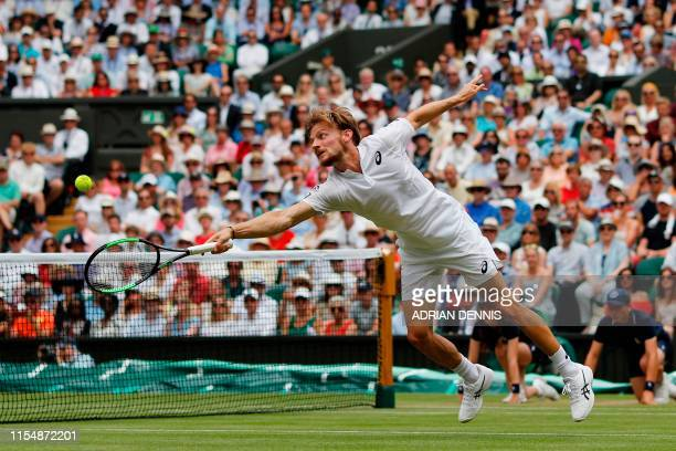 Belgium's David Goffin returns against Serbia's Novak Djokovic during their men's singles quarter-final match on day nine of the 2019 Wimbledon...