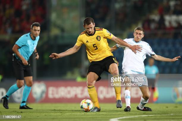 Belgium's defender Jan Vertonghen holds off San Marino's midfielder Marcello Mularoni as Romanian referee Horatiu Fesnic looks on during the Euro...
