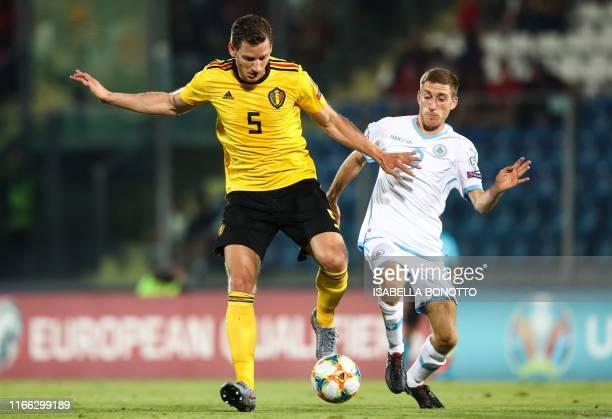 Belgium's defender Jan Vertonghen holds off San Marino's midfielder Marcello Mularoni during the Euro 2020 qualifier football match San Marino vs...