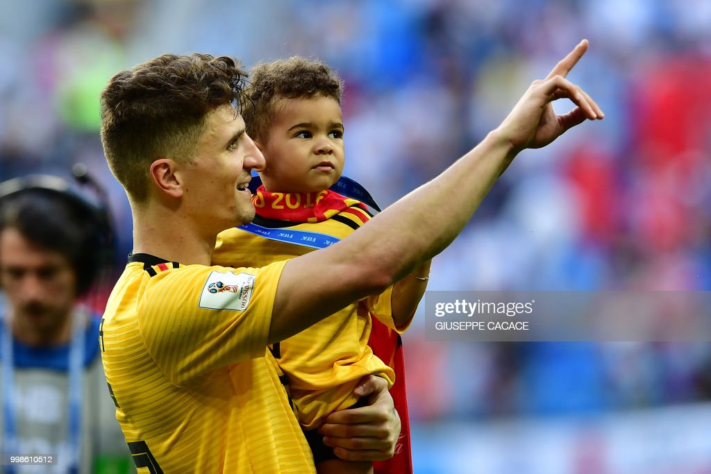 Belgium's defender Thomas Meunier (L) holds his son as he celebrates their victory after their Russia 2018 World Cup play-off for third place football match between Belgium and England at the Saint Petersburg Stadium in Saint Petersburg on July 14, 2018. (Photo by Giuseppe CACACE / AFP) / RESTRICTED