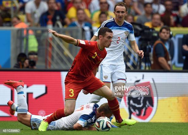 Belgium's defender Thomas Vermaelen is tackled by Russia's defender Alexei Kozlov and Russia's midfielder Oleg Shatov during the Group H football...