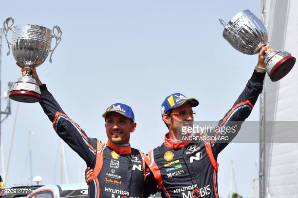 Belgium's driver Thierry Neuville and compatriot codriver Nicolas Gilsoul of Hyundai i20 Coupe WRC hold their trophies as they celebrate on the...