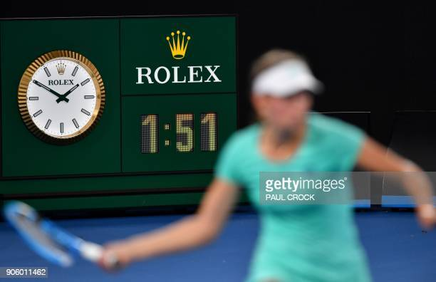 Belgium's Elise Mertens plays a shot beside a clock showing the local time during her women's singles second round match against Australia's Daria...