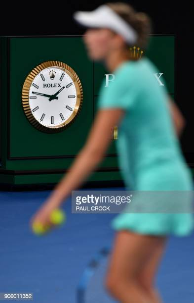 Belgium's Elise Mertens walks on court past a clock showing the local time during her women's singles second round match against Australia's Daria...