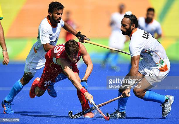 Belgium's Elliot van Strydonck vies with India's Chandanda Thimmaiah and India's Sardar Singh during the men's quarterfinal field hockey Belgium vs...