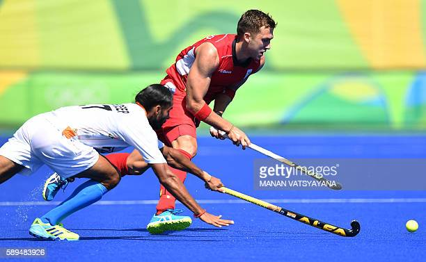 Belgium's Emmanuel Stockbroekx vies with India's Akashdeep Singh during the men's quarterfinal field hockey Belgium vs India match of the Rio 2016...