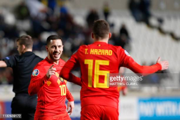 Belgium's forward Eden Hazard celebrates his goal with teammate and brother Thorgan Hazard during the Euro 2020 Group I football qualification match...