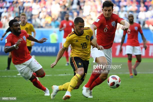 Belgium's forward Eden Hazard runs with the ball past England's defender Danny Rose and England's defender Harry Maguire during their Russia 2018...