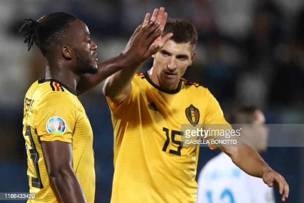 Belgium's forward Michy Batshuayi celebrates with Belgium's midfielder Thomas Meunier after scoring during the Euro 2020 qualifier football match San...