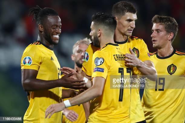 Belgium's forward Michy Batshuayi celebrates with Belgium's midfielder Yannick Ferreira-Carrasco and Belgium's midfielder Thomas Meunier after...