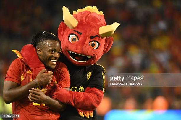 Belgium's forward Michy Batshuayi celebrates with the Red Devil Mascott at the end of the international friendly football match between Belgium and...