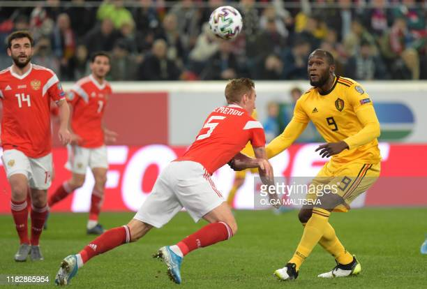 Belgium's forward Romelu Lukaku and Russia's defender Andrey Semenov vie for the ball during the Euro 2020 football qualification match between...
