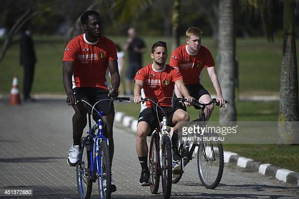 Belgium's forward Romelu Lukaku, Belgium's midfielder Dries Mertens and Belgium's midfielder Kevin De Bruyne ride their bicycles to attend a training...