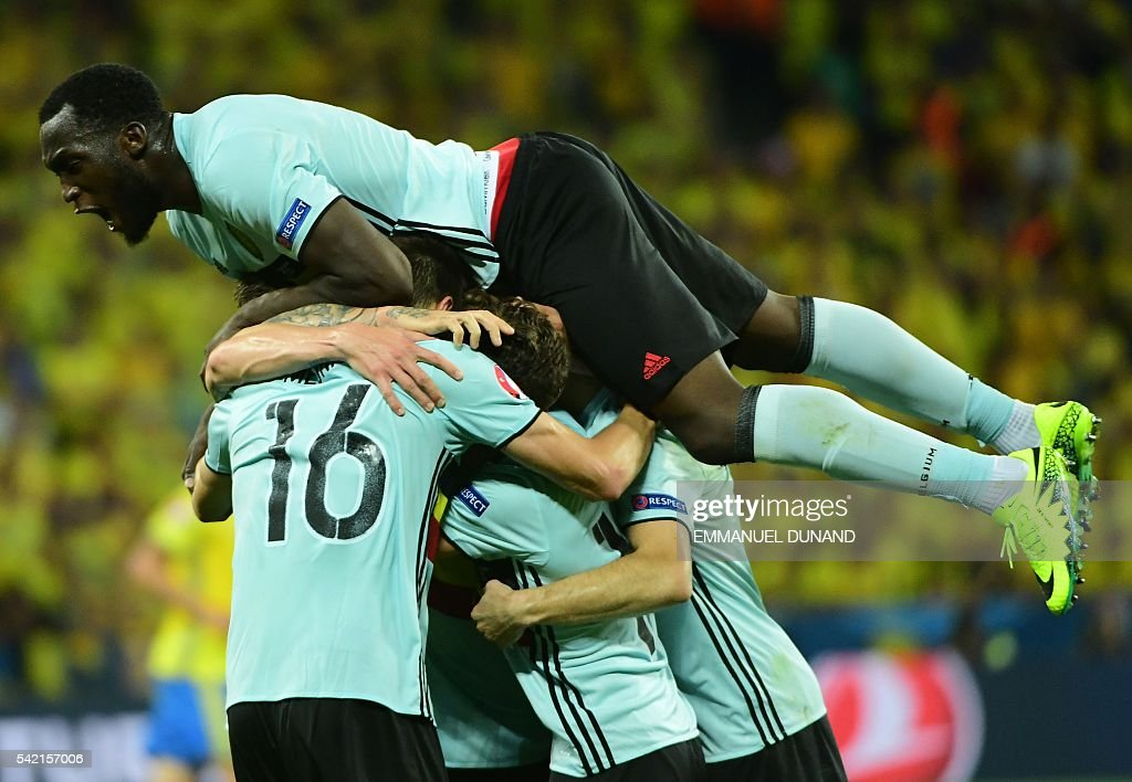 TOPSHOT - Belgium's forward Romelu Lukaku (Top) jumps over his teammates as they celebrate a goal during the Euro 2016 group E football match between Sweden and Belgium at the Allianz Riviera stadium in Nice on June 22, 2016. / AFP / EMMANUEL