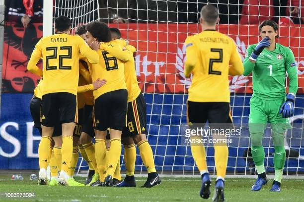 Belgium's forward Thorgan Hazard is congratulated by teammates after scoring the opening goal as Switzerland's goalkeeper Yann Sommer reacts during...