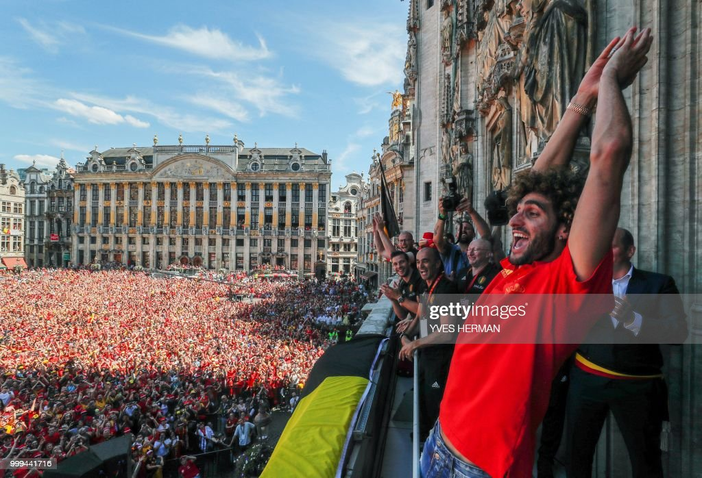 TOPSHOT - Belgium's goalkeeper Marouane Fellaini celebrates on the balcony in front of more than 8000 supporters at the Grand Place/Grote Markt in Brussels city center, as Belgian national football team Red Devils arrive to celebrate with supporters at the balcony of the city hall after reaching the semi-finals and winning the bronze medal at the Russia 2018 World Cup, on July 15, 2018. (Photo by Yves HERMAN / BELGA / AFP) / Belgium OUT