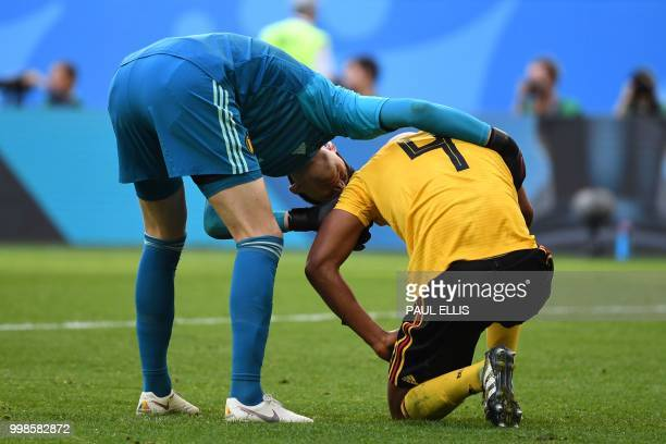 Belgium's goalkeeper Thibaut Courtois checks on Belgium's defender Vincent Kompany during their Russia 2018 World Cup playoff for third place...