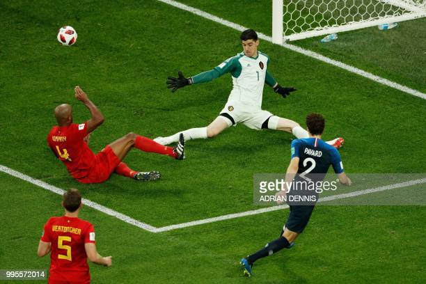 Belgium's goalkeeper Thibaut Courtois jumps to catch the ball next to Belgium's defender Vincent Kompany and France's defender Benjamin Pavard during...