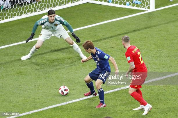Belgium's goalkeeper Thibaut Courtois looks at Yuya Osako of Japan as he attempts to shoot during the first half of a World Cup roundof16 match in...