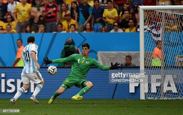Belgium's goalkeeper Thibaut Courtois prepares to block a shot at goal by Argentina's forward Lionel Messi during the second half of a quarterfinal...
