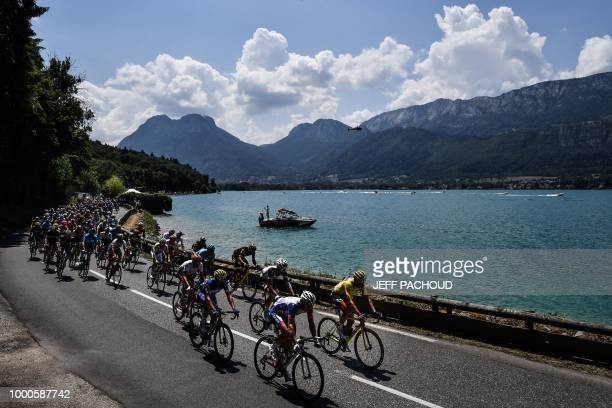 Belgium's Greg Van Avermaet , wearing the overall leader's yellow jersey, and the pack ride along the lake of Annecy during the tenth stage of the...