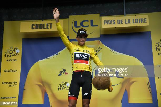 Belgium's Greg Van Avermaet wearing the overall leader's yellow jersey waves from the podium after USA's BMC Racing cycling team won the third stage...