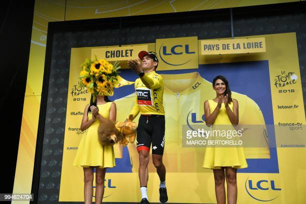 Belgium's Greg Van Avermaet wearing the overall leader's yellow jersey throws a bouquet of flowers from the podium after USA's BMC Racing cycling...